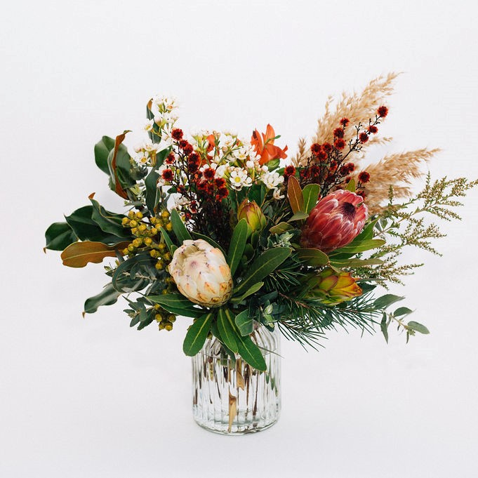 Wilderness - lush native style bouquet in vase, featuring pink or white protea, stirlingia, leucadendron, reed and gum foliage.
