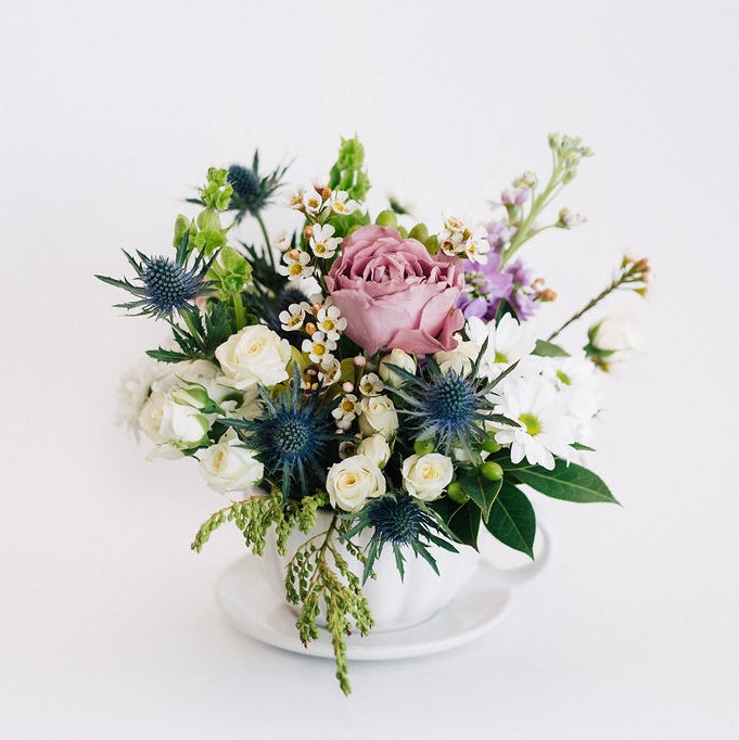 White teacup arrangement featuring blue, white and lilacs with roses, seaholly, chrysanthemums, stock and waxflower. Melbourne delivery only.