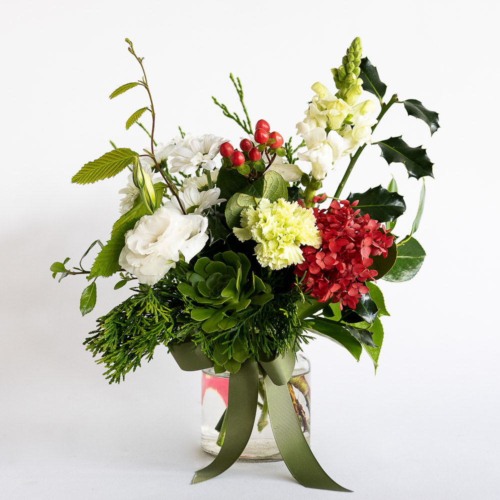 mason jar featuring sim carnations, succulent, chincherinchee, preserved red hydrangea, red hypericum, lisianthus and chrysanthemum.