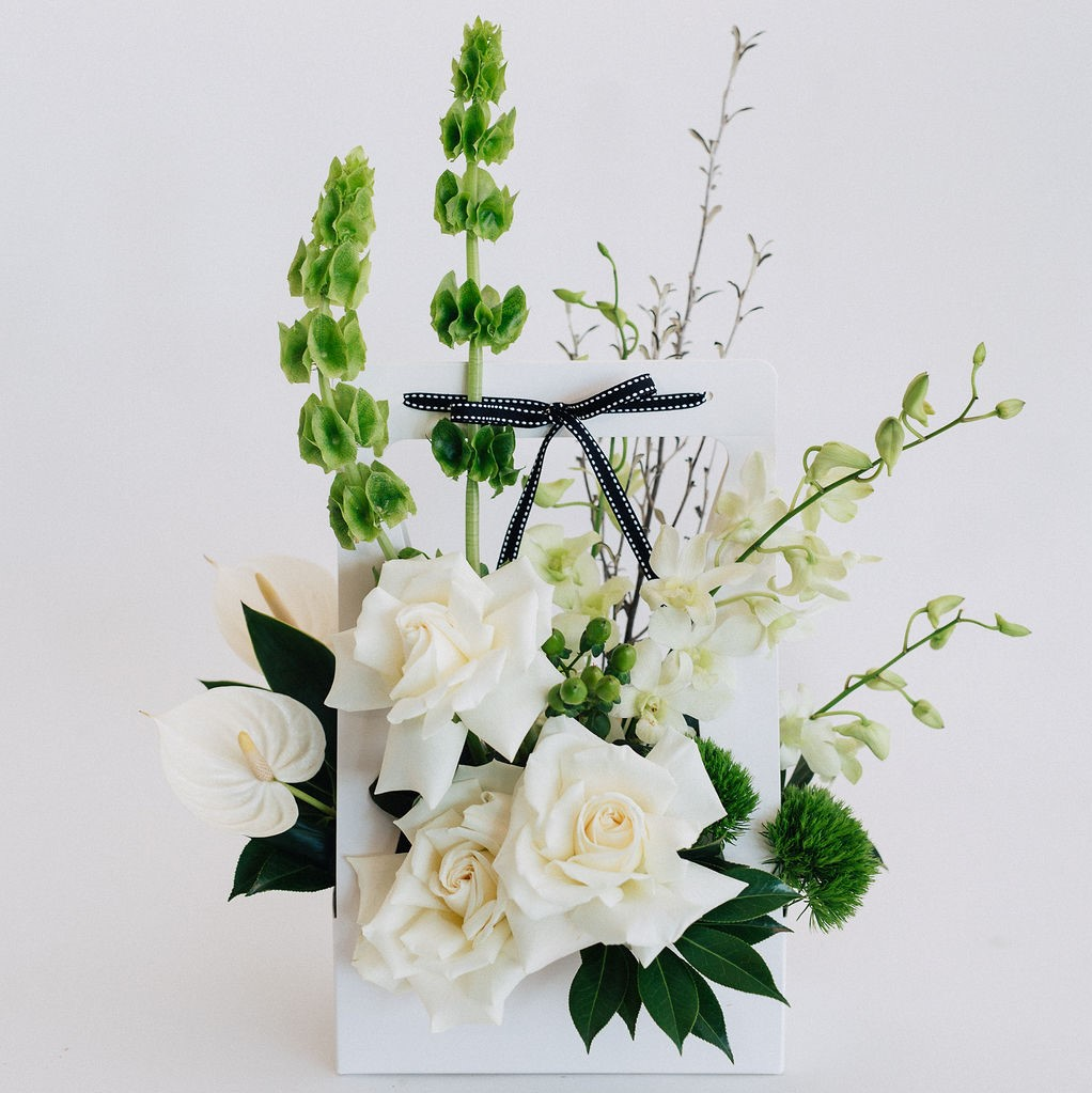 Vamos - white carry box flower arrangement featuring white reflexed roses, molucca balm, green trix and white singapore orchids.